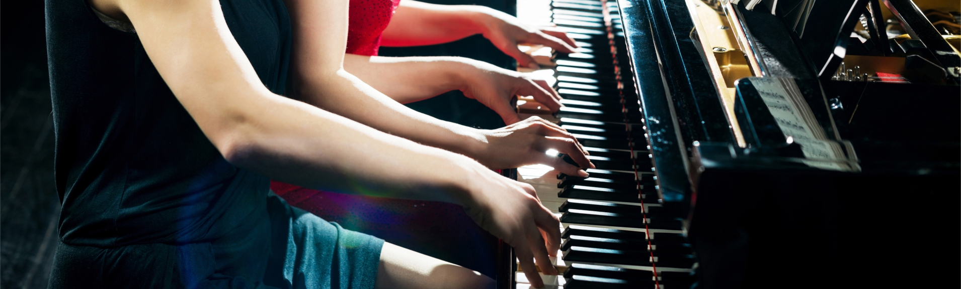 Two people playing piano