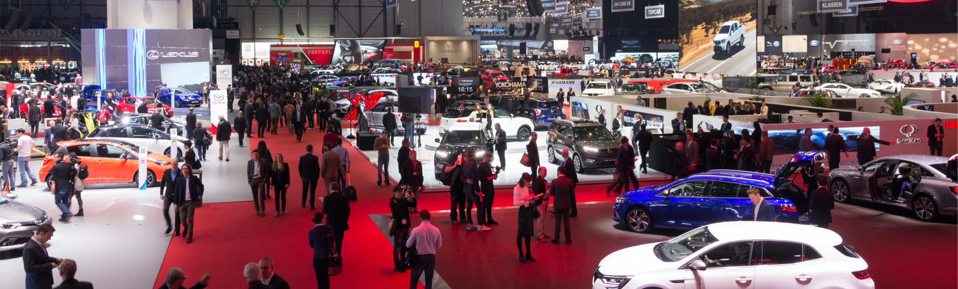 Convention center displaying automobiles with a large audience