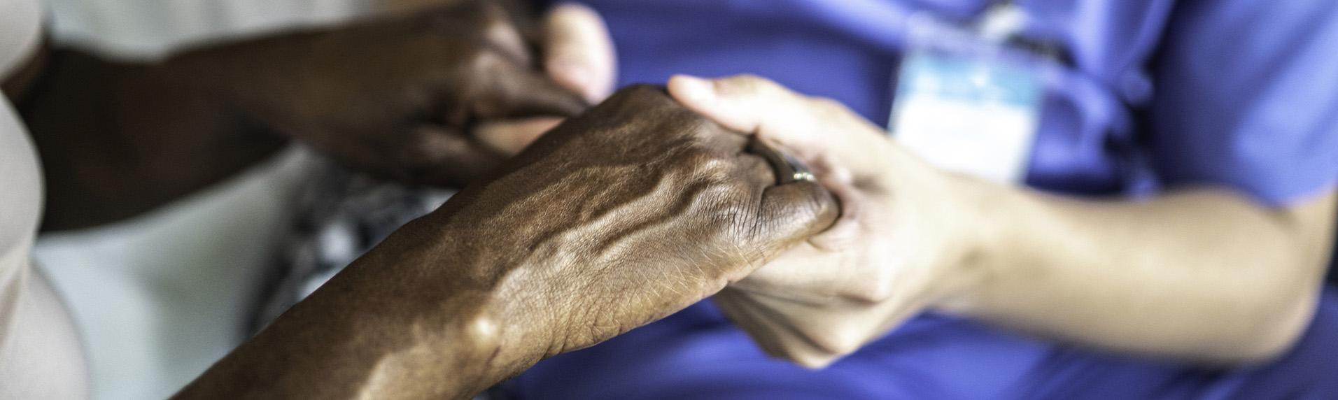 Nursing or retirement home caretaker holding hands with patient