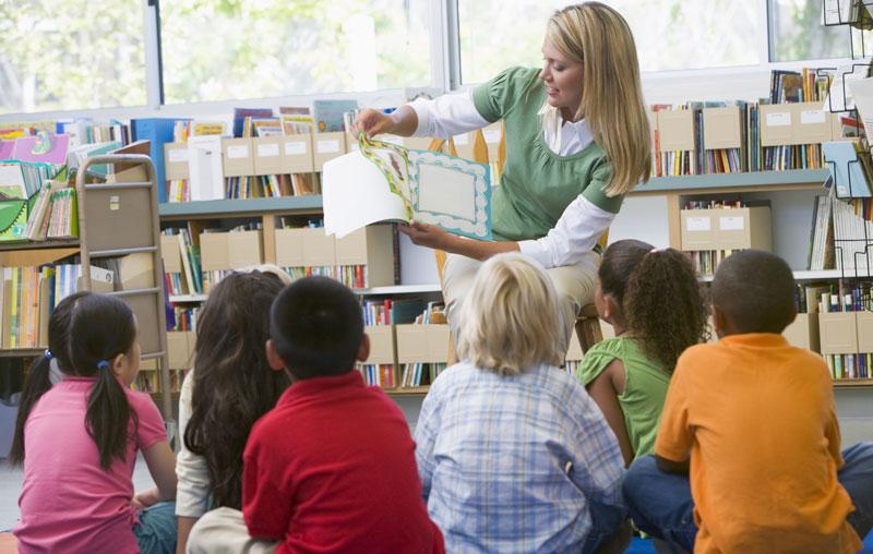 Teacher reading a book to school children