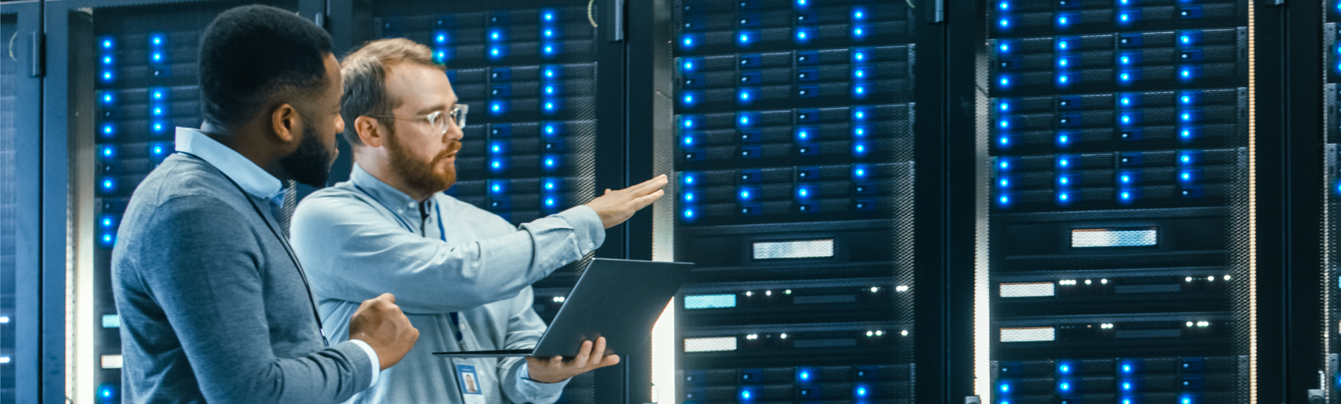 Two workers conversing in front of a large data center